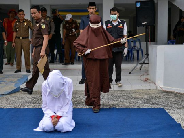 the first female flogger preparing to whip a woman in public in banda aceh after she was caught in close proximity with a man who is not her husband in a hotel photo afp file