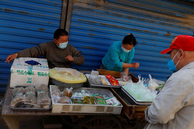 a man wearing a face mask buys food at a street stall as the spread of the coronavirus disease covid 19 continues in beijing china april 24 2020 photo reuters