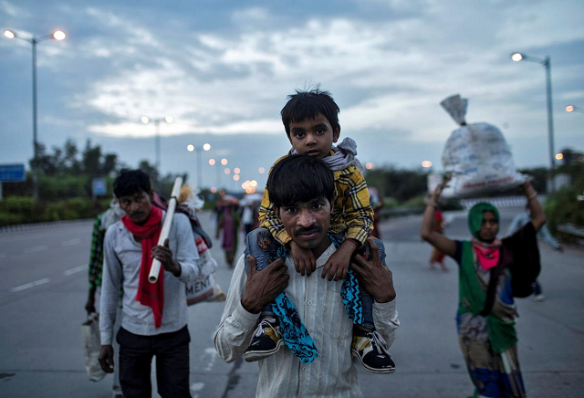 dayaram kushwaha a migrant worker carries his 5 year old son shivam on his shoulders as they walk along a road to return to their village during a 21 day nationwide lockdown to limit the spreading of coronavirus in new delhi india march 26 2020 photo reuters