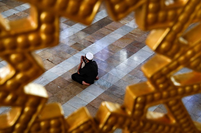 a muslim man wearing a protective face mask prays at a mosque on april 24 in bangkok thailand photo reuters
