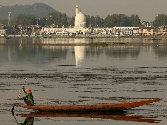 woman in indian occupied kashmir rows her boat with revered hazratbal shrine in the backdrop on the first day of ramazan in srinagar photo aa file