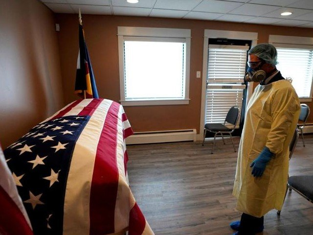 michael neel funeral director of of all veterans funeral and cremation wearing full ppe looks at the us flag on the casket of george trefren a 90 year old korean war veteran who died of the coronavirus disease covid 19 in a nursing home in denver colorado photo reuters