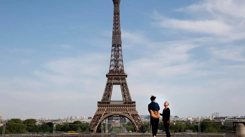 people wearing a face mask stand on the empty trocadero esplanade near the eiffel tower in paris photo afp