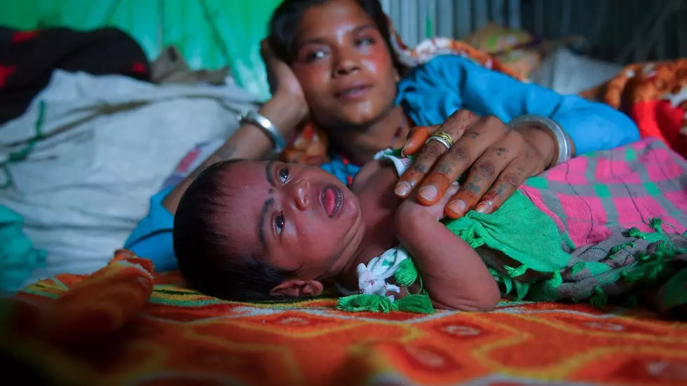 Manju Bauri rests with her newborn baby boy 'Lockdown' in their temporary home in northeast India. PHOTO: AFP