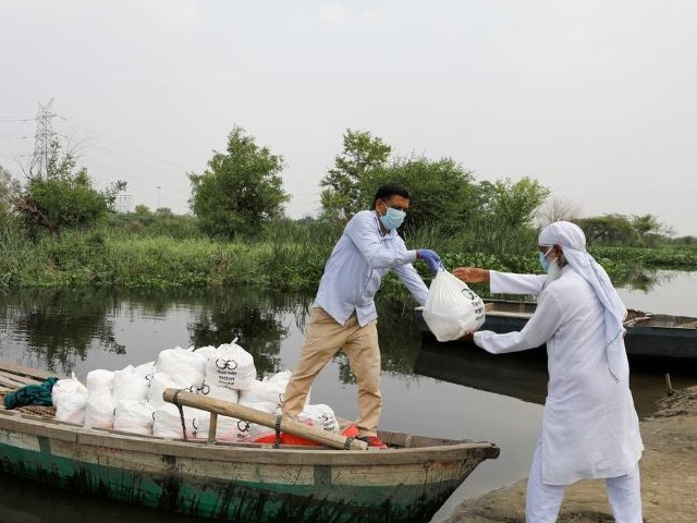 a man gives food to a volunteer to distribute to residents living in a slum on the banks of yamuna river during an extended nationwide lockdown to slow the spread of the coronavirus disease covid 19 in new delhi india photo reuters file