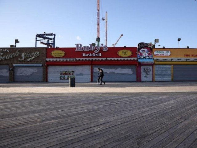 people wearing protective masks walk past closed shops on the the coney island boardwalk during the outbreak of coronavirus disease covid 19 in brooklyn new york us photo reuters file