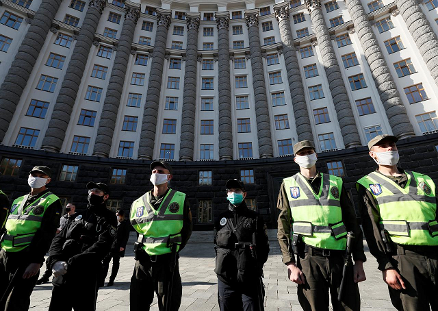 police officers and members of the national guard of ukraine stand guard during a protest to demand support from the government for small businesses and easing of lockdown measures put into place because of the coronavirus disease covid 19 outbreak in front of the ukrainian cabinet of ministers building in central kiev ukraine april 29 2020 photo reuters