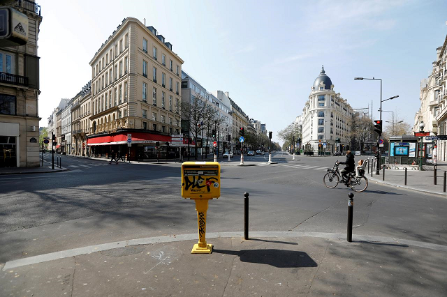 a cyclist rides on the deserted grands boulevards in paris as a lockdown is imposed to slow the rate of the coronavirus disease covid 19 in france march 27 2020 photo reuters