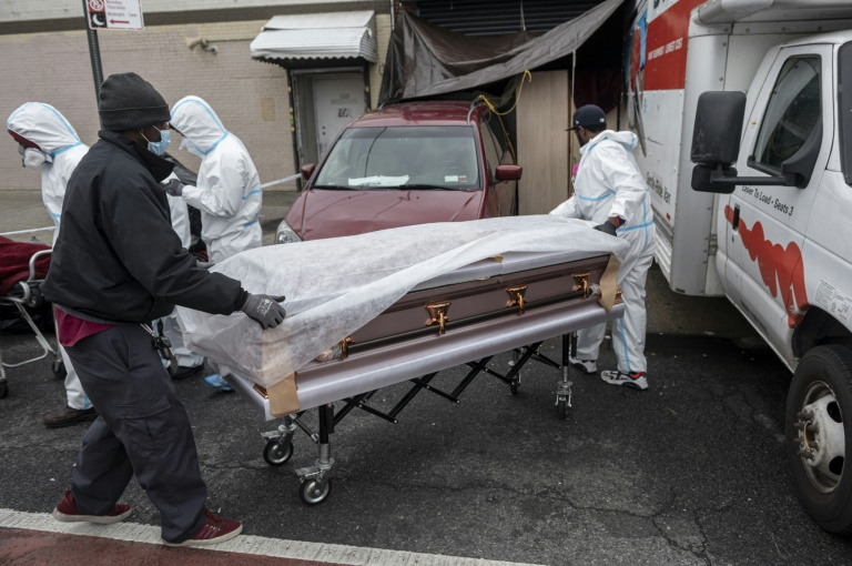 People in hazmat suits and masks shift a casket into a funeral home in Brooklyn on April 30, 2020 where dozens of decomposing bodies were found in trucks. Photo: AFP
