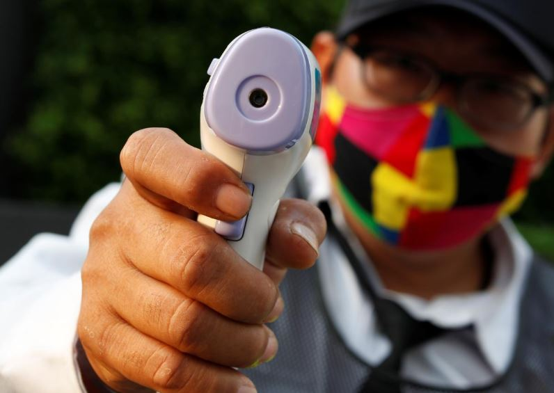a security guard wearing a protective mask points a thermometer gun as he stands at the entrance of a condominium building amid the coronavirus disease covid 19 outbreak in bangkok thailand photo reuters
