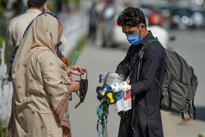 a street vendor wearing a facemask as a preventive measure against the covid 19 interacts with customers alongside a street in islamabad photo afp file