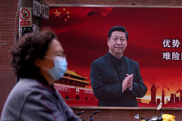 a woman wearing a protective mask is seen past a portrait of chinese president xi jinping on a street as the country is hit by an outbreak of the coronavirus in shanghai china march 12 2020 reuters