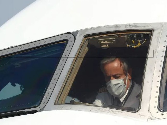 a pilot wearing a protective mask is seen in a cargo aircraft chartered by the un world food programme with medical supplies to help developing countries hit by the coronavirus disease covid 19 outbreak at liege airport belgium photo reuters file