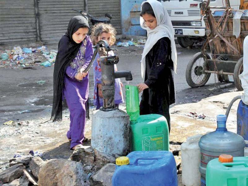 Young girls fill water in cans from a hand pump. The city's residents have long been struggling with water woes due to shortfalls, leaky pipes and theft. PHOTO: FILE