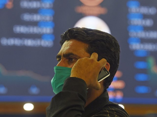 A stockbroker wearing a facemask amid concerns over the spread of the COVID-19 novel coronavirus, holds a mobile phone during a trading session at the Pakistan Stock Exchange (PSX) in Karachi on March 16, 2020. PHOTO: AFP