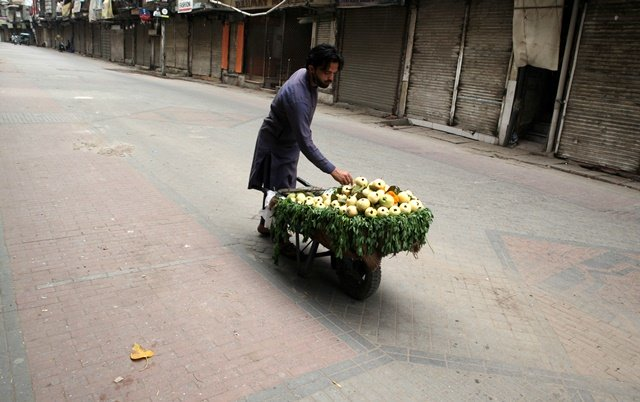 a fruit vendor waits for customers as he sells guava from a wheelbarrow along a closed market during a lockdown following an outbreak of coronavirus disease covid 19 in lahore pakistan march 31 2020 reuters mohsin raza