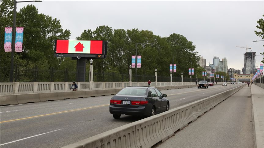 a canadian flag with a red house replaced the maple leaf urging canadians to stay at home during the coronavirus pandemic covid 19 is seen on burrard street bridge in vancouver canada photo aa