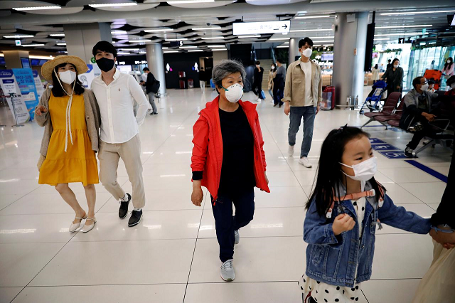 people wearing masks to avoid the spread of the coronavirus disease covid 19 arrive at gimpo international airport in seoul south korea may 1 2020 photo reuters