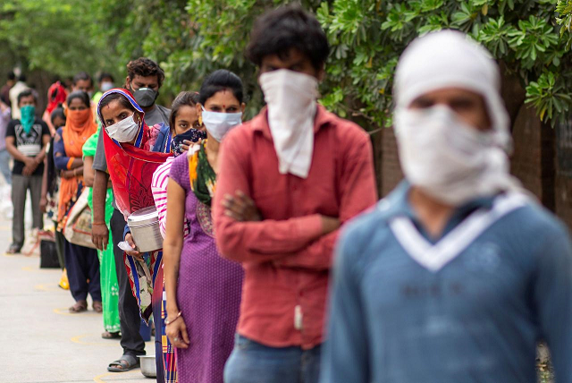 people wait to receive free food at an industrial area during an extended nationwide lockdown to slow the spreading of the coronavirus disease covid 19 in new delhi india april 23 2020 photo reuters