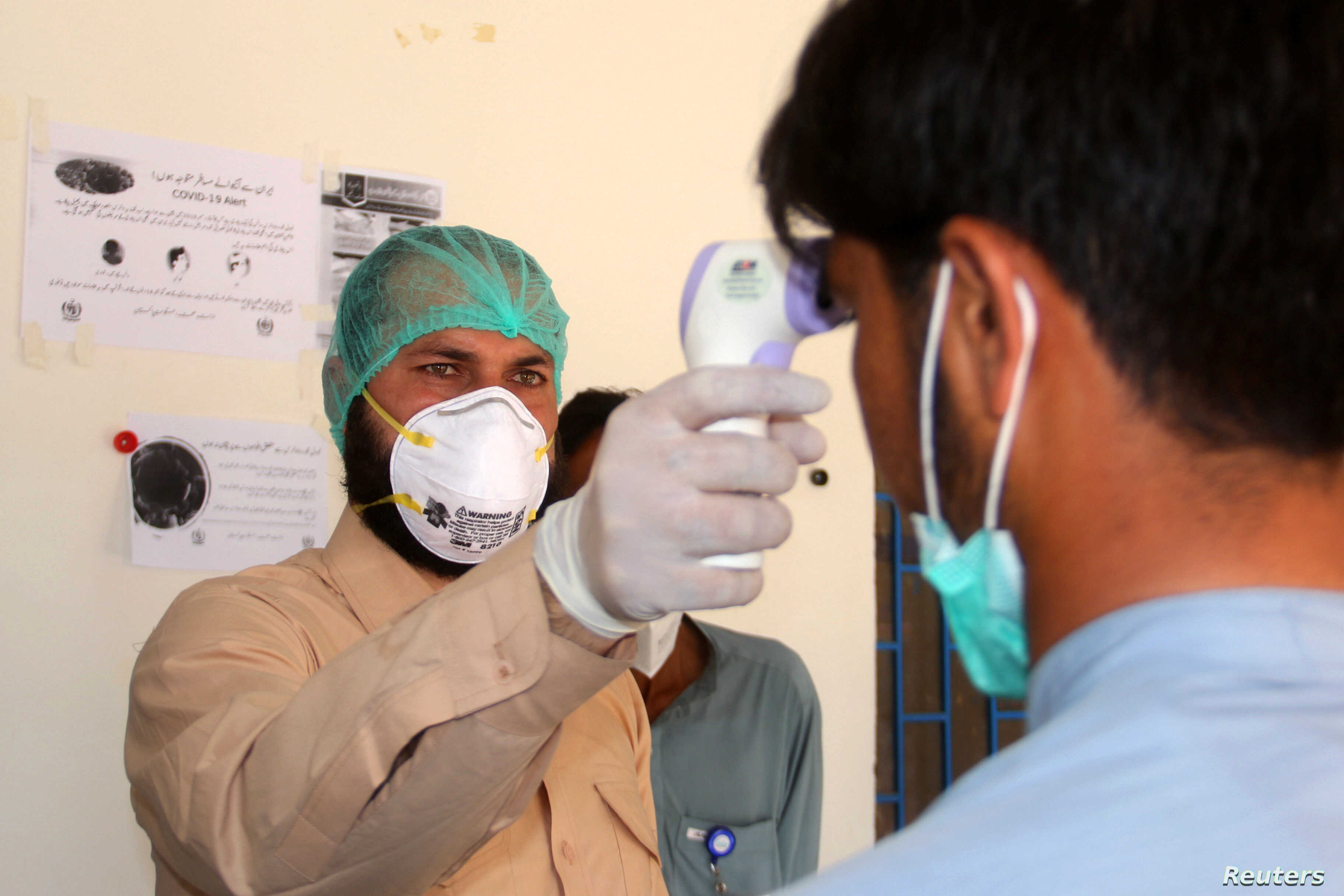 a health worker takes the temperature of a man who returned from iran and is under medical observation after pakistan sealed its border with iran as a preventive measure following the coronavirus outbreak at the border post in taftan pakistan february 25 2020 reuters naseer ahmed