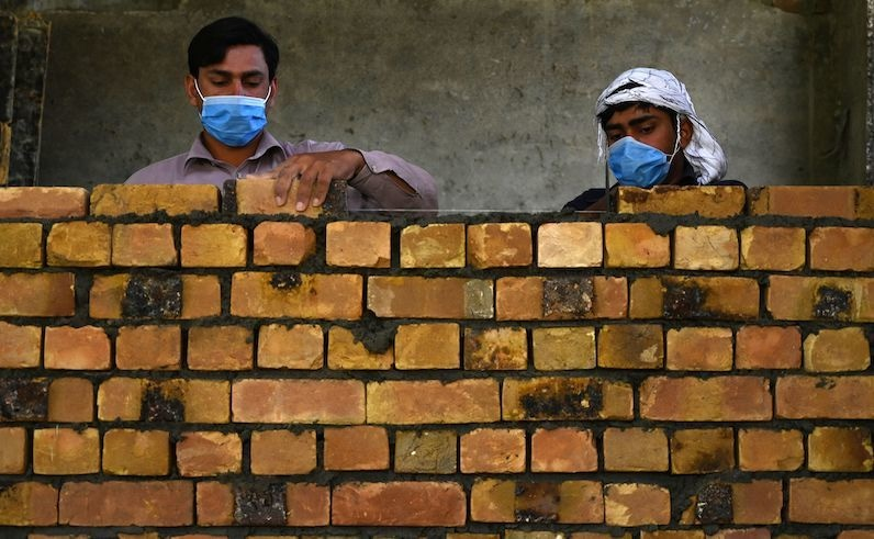 workers wearing facemasks lay a brick wall at a construction site in islamabad photo afp file