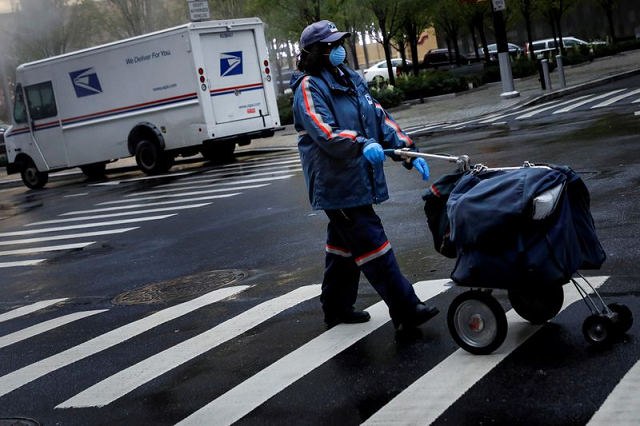 a united states postal service usps worker works in the rain in manhattan during the outbreak of the coronavirus disease covid 19 in new york city new york us april 13 2020 photo reuters