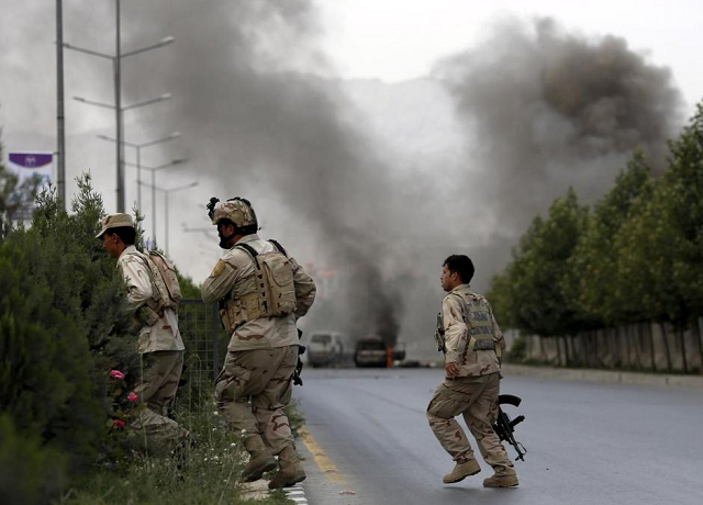 members of afghan security forces cross a road as smoke billows from the site of an attack near the afghan parliament in kabul photo reuters