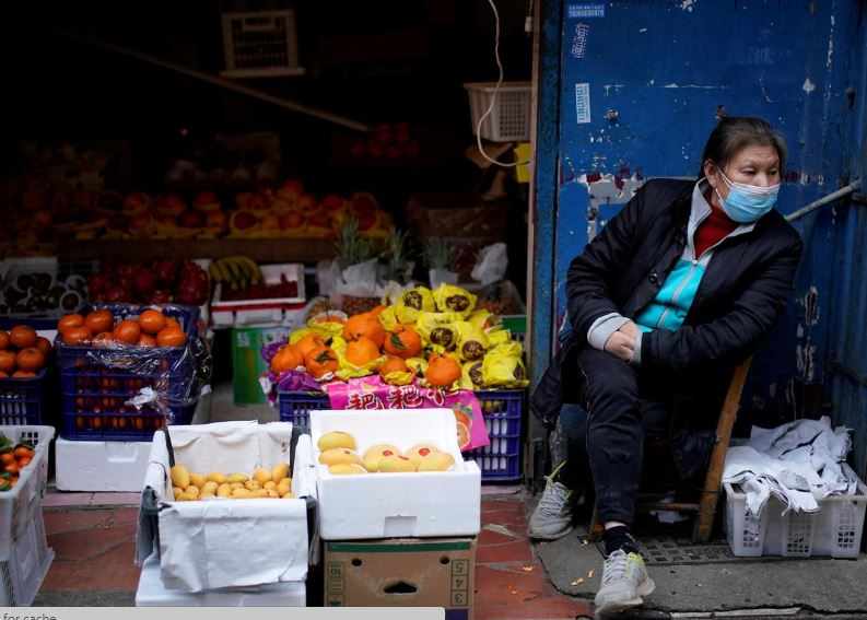 a woman wearing a face mask sits next to a fruit stall at a residential area after the lockdown was lifted in wuhan capital of hubei province and china 039 s epicentre of the novel coronavirus disease covid 19 outbreak photo reuters