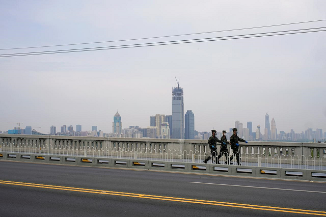 paramilitary officers wearing face masks walk on a bridge over yangtze river after the lockdown against the coronavirus disease covid 19 was lifted in wuhan hubei province china april 14 2020 photo reuters