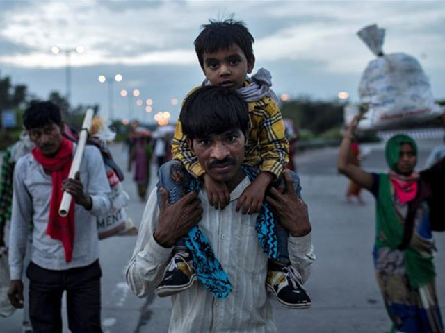 a migrant worker carries his son as they walk along a road with others to return to their village during lockdown in india photo reuters file