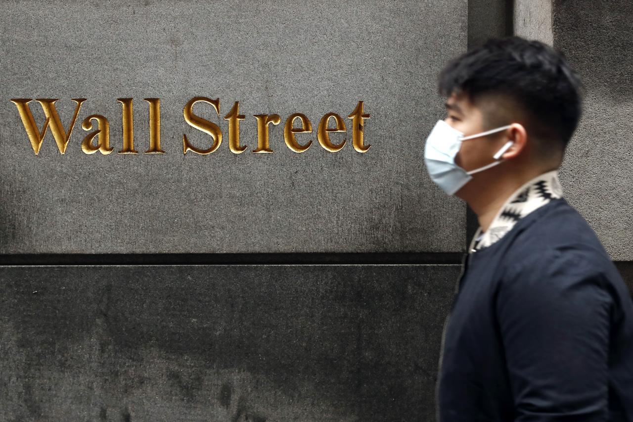 a reuters image of a man wearing a mask along the wall street