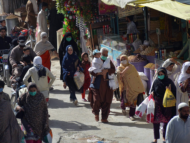 people walk in a market for shopping after the government eased a nationwide lockdown imposed as a preventive measure against the covid 19 in quetta on saturday photo afp