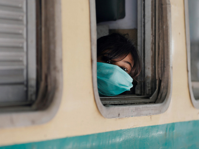 a-girl-wearing-a-protective-mask-looks-out-from-a-train-window-as-she-returns-to-her-hometown-in-karachi-photo-reuters-file