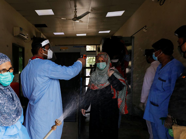 Railway workers wearing protective gears measure the temperature and disinfect passengers before they board a train in Karachi. PHOTO: REUTERS/FILE
