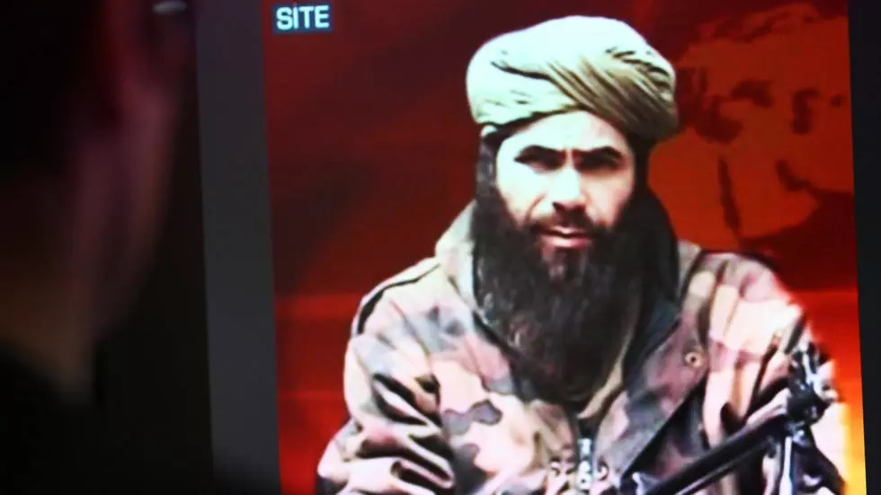In this file photo taken on November 19, 2010, a man looks at a picture of Abdelmalek Droukdel, aka Abu Musab Abdul Wadud, head of al Qaeda  Maghreb seen on US monitoring group SITE Intelligence, in Paris. PHOTO: AFP
