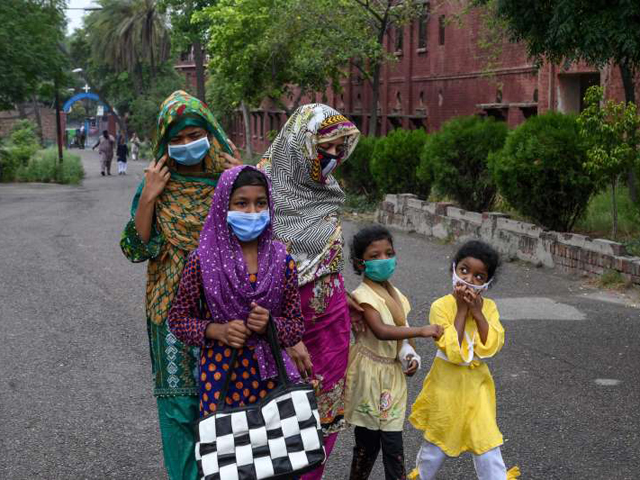 A Catholic family wearing facemasks arrives to attend Sunday prayers at the Mary Immaculate Church in Lahore. PHOTO: AFP/FILE