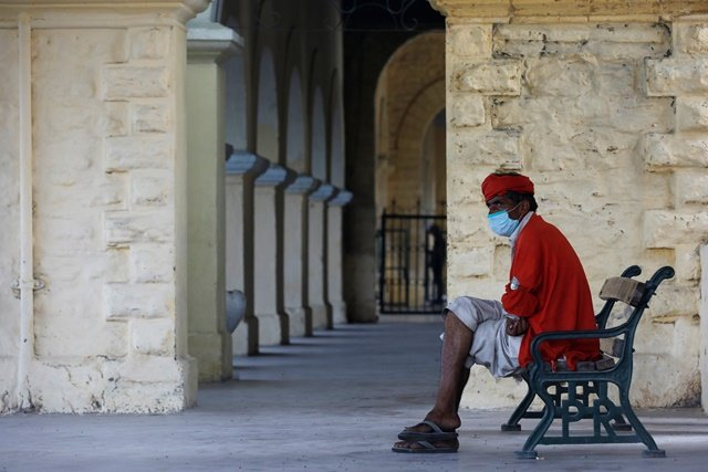 A porter, also known as a coolie, wears a protective mask as he waits for passengers to offer his service at a railway station, as the outbreak of the coronavirus disease (COVID-19) continues, in Karachi, Pakistan June 9, 2020. REUTERS