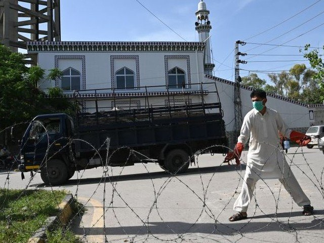 a plain clothes policeman wearing a facemask seals off a street with barbed wire at a residential area in islamabad as a preventive measure against the covid 19 photo afp file