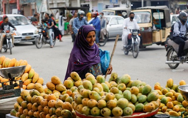 A woman walks past mango stalls at the retail market, as the outbreak of the coronavirus disease (COVID-19) continues, in Karachi, Pakistan June 11, 2020. REUTERS/Akhtar Soomro