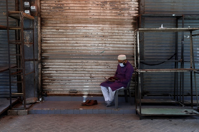 A shopkeeper with his shoes off reads the Quran, outside his closed shop at a market after Pakistani authorities re-imposed lockdown in selected areas as an effort to stop the spread of the coronavirus disease (COVID-19), in Karachi, Pakistan June 19, 2020. PHOTO: REUTERS