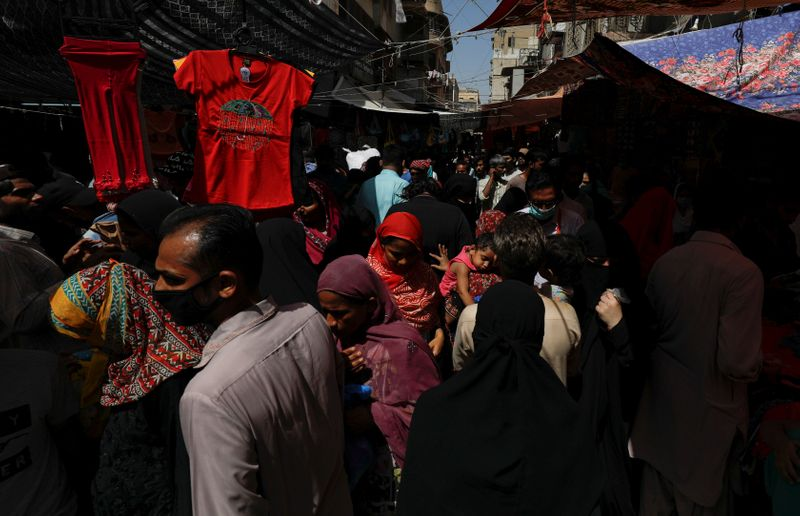 People pass on each other as they shop from stalls in a market after Pakistan started easing the lockdown restrictions. PHOTO: REUTERS