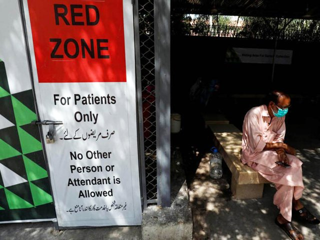 A man sits at the waiting area outside a sample collection facility for the coronavirus testing in Karachi. PHOTO: REUTERS/FILE