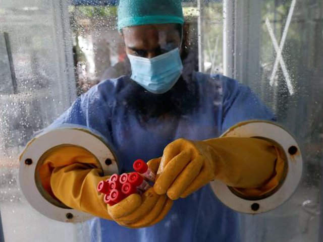 A paramedic wearing protective gear at a glass booth, counting nose-swab samples to be tested for the coronavirus disease in Karachi. PHOTO: REUTERS/FILE