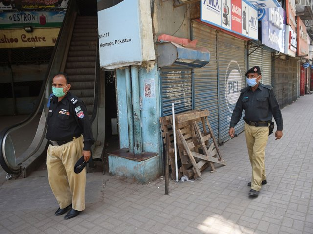 Policemen guard a blocked street which was sealed by the authorities in Karachi. PHOTO: AFP/FILE