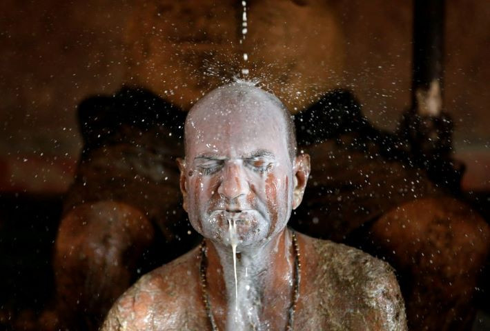 Ashok Oza bathes in cow milk to remove cow dung from his body during