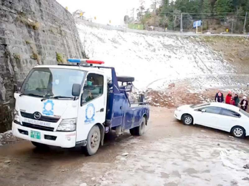 a police truck tows a stranded car in murree during snowfall photo express