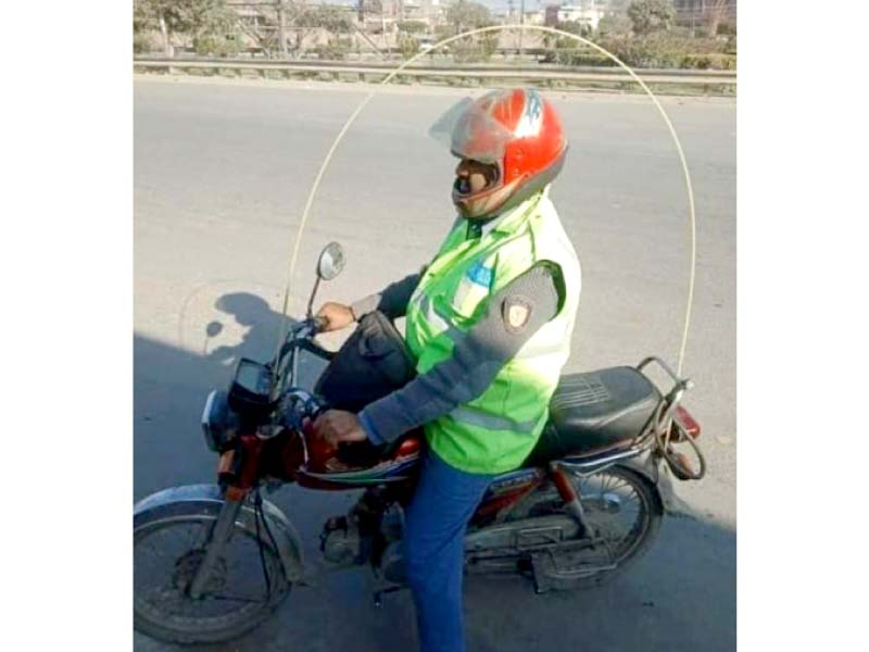 a traffic police official on his bike with a safety cable attached to prevent kite strings from getting entangled around his neck photo express