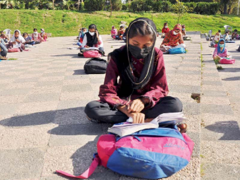 with educational institutions closed given the rising covid cases mask clad students observe all sops as they attend an open air class arranged by an informal school in the federal capital photo nni
