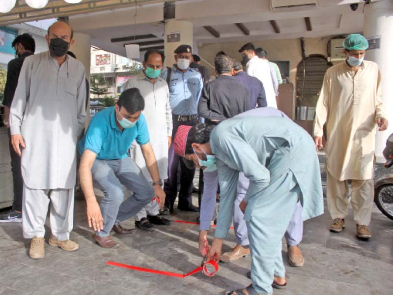 city magistrate ghulam mustafa chandio supervises margin lines being marked outside markets in the blue area to maintain social distancing while queuing up to shops in the federal capital photo online