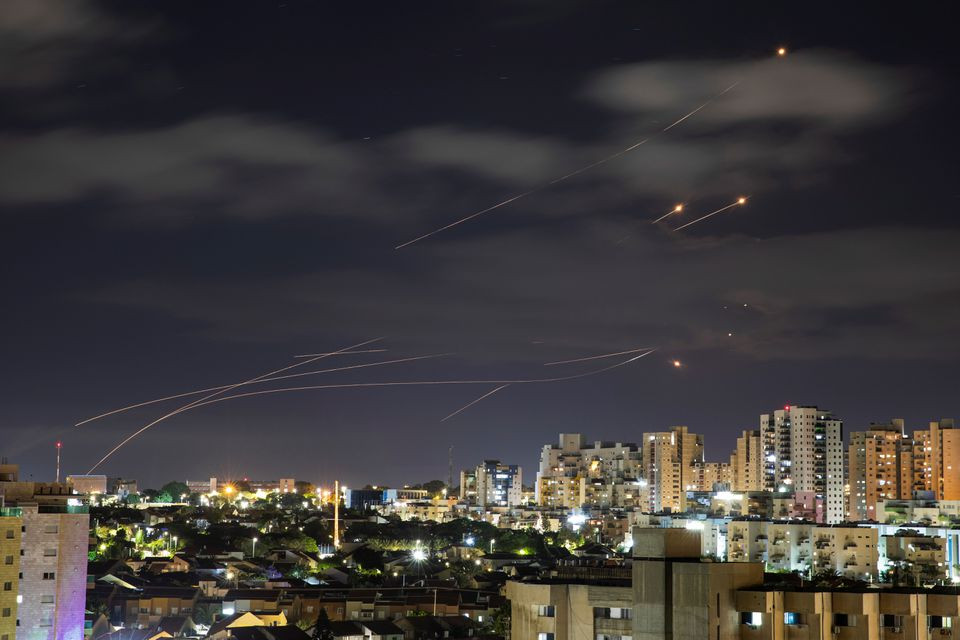 Streaks of light are seen as Israel's Iron Dome anti-missile system intercepts rockets launched from the Gaza Strip towards Israel, as seen from Ashkelon, Israel May 17. PHOTO: REUTERS